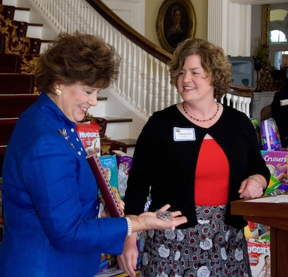 "Alabama's First Lady Patsy Riley receives an Air Command and Staff College cookbook and coin from Annette Roberts, representing ACSC spouses. Several of ACSC spouses were at the Governor's Mansion Feb. 12 to present the results of the school's ""Diaper Drive"" for the Montgomery Family Sunshine Center, one of Mrs. Riley's charitable interests which supports victims of domestic violence in the Montgomery area. (Air Force photo by Jamie Pitcher)"
