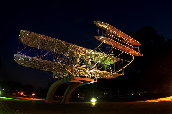 A view of the monument photographed at night shows the sculpture of Orville Wright at the flyer's controls. The monument was dedicated Sept. 18, 1985, during a large ceremony that included rides in a flying model of a 1917 Wright Brothers aircraft. (Air Force photo by Donna Burnett)