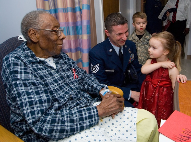 Richard Lockhart, a patient at Montgomery Veteran's Hospital, receives a valentine Feb. 13 from Katelynn Nelson, age 3.  Also shown are Katelynn's 5-year-old brother Christopher, and father Tech. Sgt. Jason Nelson. They were all volunteers for the local salute to hospitalized veterans sponsored by the National Department of Veterans' Affairs. (Air Force photo by Melanie Rodgers Cox)