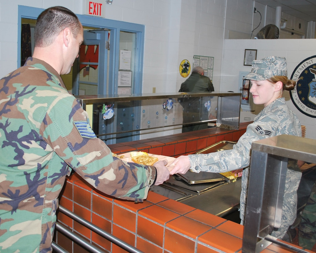 Senior Airman Kelsi Larsen serves Tech. Sgt. Patrick Marino breakfast during annual training at Volk Field, Wis. Jan. 9th.  Members of the 114th Security Forces Squadron and the 114th Services Flight worked together to complete two weeks annual training in the wintery environment.