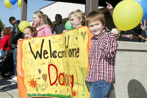 """Dobbins Air Reserve Base, Ga. - Family members of a 94th Security Forces Squadron Airman returning from Iraq display a welcome home banner for """"Daddy"""" while waiting with other families to meet and greet their loved ones from a six-month deployment.  Approximately 26 Airmen of the 94th Security Forces Squadron were deployed to Iraq in support of Operation Iraqi Freedom.  (U.S. Air Force photo/Don Peek)"""