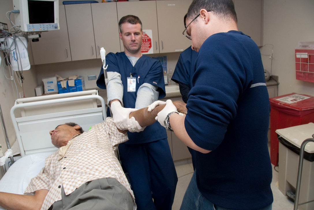 Capt Brian Corwin and Orthopedic Technician Melvin Cruz pull traction on a patient with a broken arm to prepare for casting. Members of the 185th Air Refueling Wing, Iowa Air National Guard, Medical Squadron, deployed to Centro Medico, Hospital in San Juan, Puerto Rico.   Official Air Force Photo by: TSGT. Oscar M. Sanchez