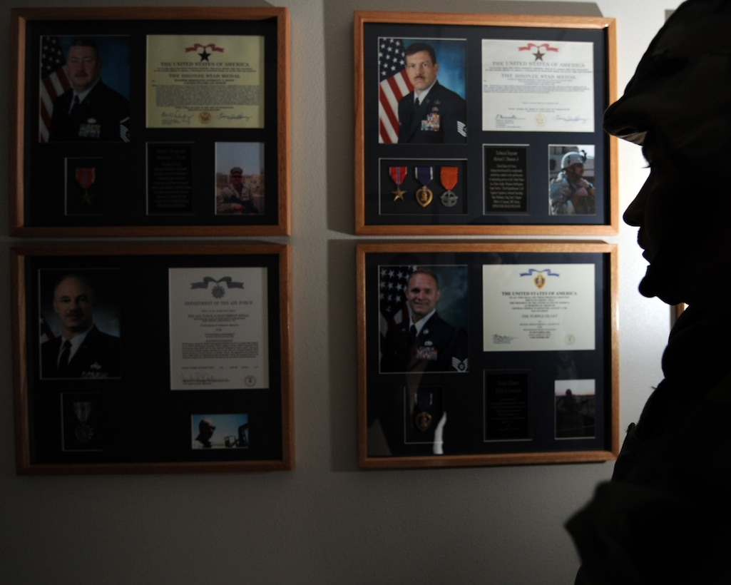 """WHITEMAN AIR FORCE BASE, Mo. - An Airman in full """"battle rattle"""" observes the Heritage Wall in Whiteman's Professional Development Center. The wall, to be headed """"A Legacy of Valor: Airmen in the Fight,"""" honors airmen through chief master sergeants recognized for outstanding achievement, exceptionally meritorious service, actions of valor and wounds received in action. (U.S. Air Force photo/Staff Sgt. Charles Larkin)"""