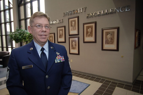 Master Sgt. Jeff Kunkle, the artist who painted the sepia-tone portraits included in the display, stands in front of the Wall of Honor, which was dedicated in a ceremony at Gunter Annex's Senior NCO Academy on Tuesday. The display honors the six enlisted Airmen who received the Medal of Honor for their actions. (Air Force photo by Melanie Rodgers Cox)