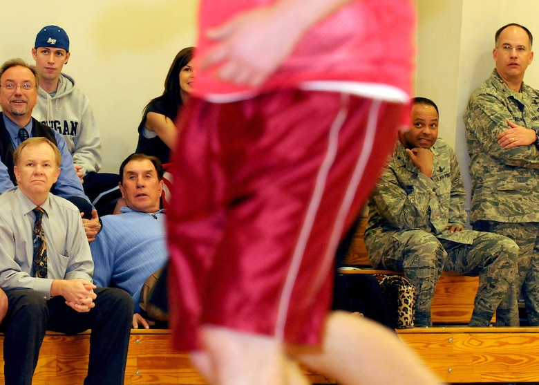 Rudy Tomjanovich (in blue sweater), former NBA champion, gold medal head coach of the Houston Rockets and the Men's Basketball team for the 2000 Olympics, and former head coach of the Los Angeles Lakers, watches as team MCSW compete in an intramural basketball game, Feb. 12.  Brig. Gen. Samuel Greaves (second from right), Military Satellite Communications Systems Wing commander, and Col. Arnold Streland (right), MILSATCOM Wing TSAT Space Group commander,  also enjoy the game. Coach Tomjanovich visited the Space and Missile Center to support the troops as an invitation from his personal friend, Tom Meseroll, MILSATCOM Chief Engineer's Office senior contractor. He stayed to watch team MCSW play its Intramural Basketball league game at the base gymnasium. (Photo by Stephen Schester) (released)