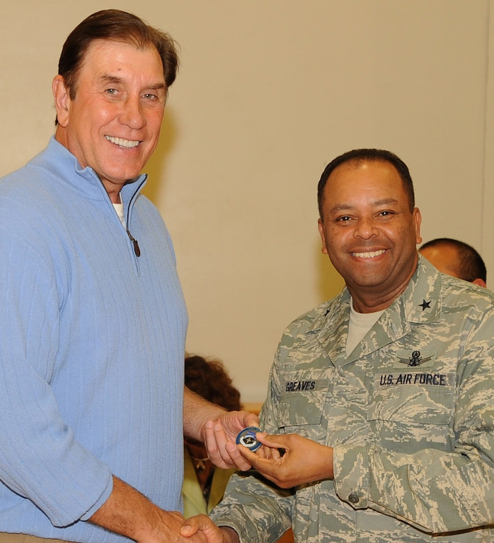 Brig. Gen. Samuel Greaves (right), MILSATCOM Wing commander, presents a unit coin to Rudy Tomjanovich, former NBA champion, gold medal head coach of the Houston Rockets and the Men's Basketball team for the 2000 Olympics, and former head coach of the Los Angeles Lakers, Feb. 12.  Coach Tomjanovich visited the Space and Missile Center to support the troops as an invitation from his personal friend, Tom Meseroll, MILSATCOM Chief Engineer's Office senior contractor. He stayed to watch team MCSW play its Intramural Basketball league game at the base gymnasium. (Photo by Stephen Schester) (released)