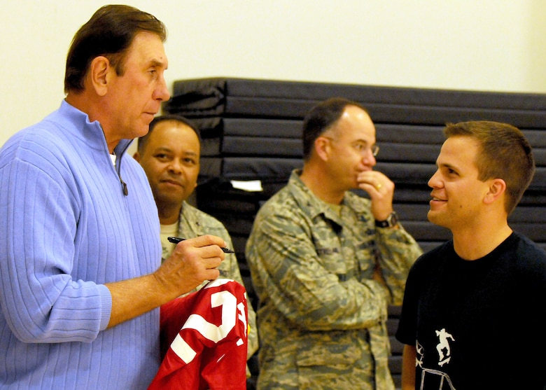 Rudy Tomjanovich (left), former NBA champion, gold medal head coach of the Houston Rockets and the Men's Basketball team for the 2000 Olympics, and former head coach of the Los Angeles Lakers, autographs a Houston Rockets jersey for 1st Lt. Erik Torguson, Military Satellite Communications Systems Wing, before the intramural basketball game for the MILSATCOM Wing team, Feb. 12. Brig. Gen. Samuel Greaves (back, left), MILSATCOM Wing commander, and Col. Arnold Streland, MILSATCOM Wing TSAT Space Group commander, look on. Coach Tomjanovich visited the Space and Missile Center to support the troops as an invitation from his personal friend, Tom Meseroll, MILSATCOM Chief Engineer's Office senior contractor. He stayed to watch team MCSW play its Intramural Basketball league game at the base gymnasium. (Photo by Stephen Schester) (released)