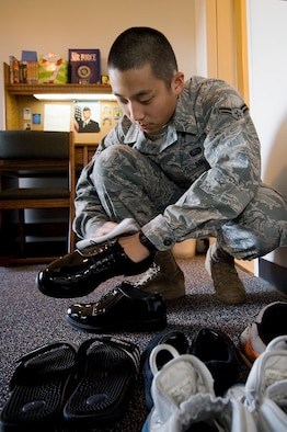Airman 1st Class Daniel Kim, a technician in the 62nd Force Support Squadron career developement section, shines his shoes as part of his daily cleaning regimen. Airman Kim was recently presented a coin after a wing inspector was amazed with how clean he kept his room. (U.S. Air Force photo/Abner Guzman)