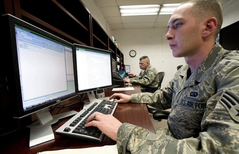 Senior Airman Kyle Stackman (front) and Tech. Sgt. James Thoni with the Information Protection Operations office at Nellis Air Force Base, Nev., monitor the base's computer network to keep it secure.  Airman Stackman is an information protection operations journeyman with the 99th Communication Squadron and Sergeant Thoni is an information protection operations technician on temporary duty to Nellis from the 28th Communications Squadron at Ellsworth AFB, S.D.  (U.S. Air Force photo/Master Sgt. Jack Braden)