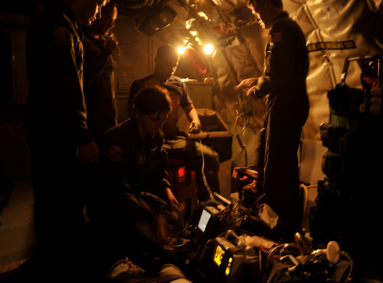 Aeromedical Evacuation Airmen work within the dark confines of a KC-135 Stratotanker flown by members of the 931st Air Refueling Group during a training mission. Air Force officials recently tested a modification that provide more electrical outlets on KC-135s for medical equipment. (U.S. Air Force photo/Tech. Sgt. Jason Schaap)