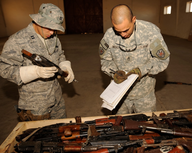 TAJI, Iraq -- Capt. Ted Yang, J4 Taji Liaison Officer, calls out the serial number of an AK-47 rifle to Army Sgt. 1st Class Alejandro Jimenez, Multi-National Security Transition Command - Iraq J4, Collective Weapons Point non-commissioned officer in charge, as he records the number at Taji Military Base, Iraq. All captured enemy weapons are accounted for before they are packaged up and shipped to be destroyed. (U.S. Air Force photo/Staff Sgt. Paul Villanueva II)