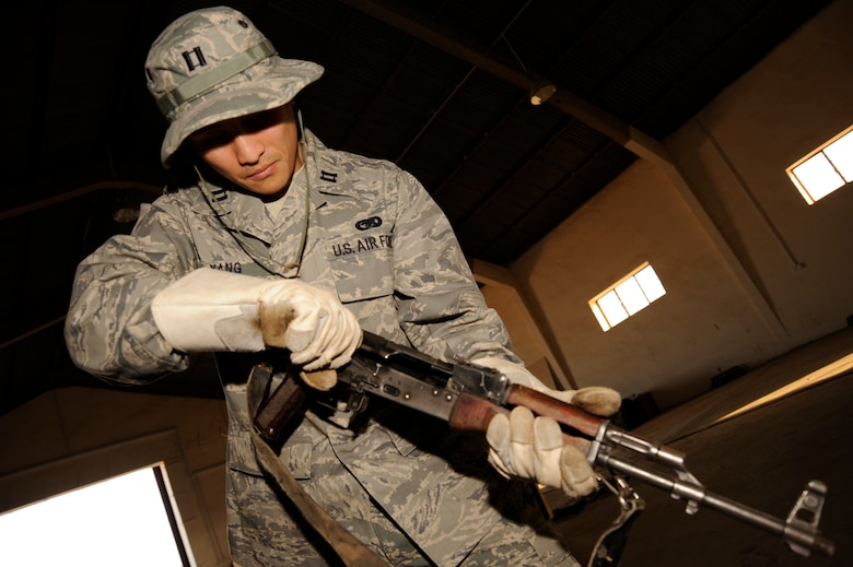 TAJI, Iraqi -- Capt. Ted Yang, J4 Taji Liaison Officer, ensures an AK-47 rifle is cleared before packing it to be shipped at Taji Military Base, Iraq. Yang, a Fresno, Calif. native, is deployed from the 509th Logistics Readiness Squadron, Whiteman, Mo. (U.S. Air Force photo/Staff Sgt. Paul Villanueva II)