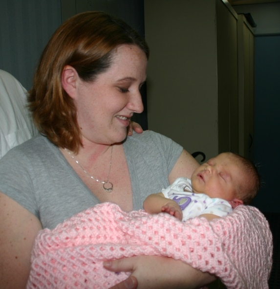 Senior Airman Stephanie Goeders, 552nd Air Control Networks Squadron, looks adoringly at her newborn baby, Emily Anne Goeders, the first baby born in 2009 in the Oklahoma City metro area. Photo courtesy of 1Lt Kinder Blacke.