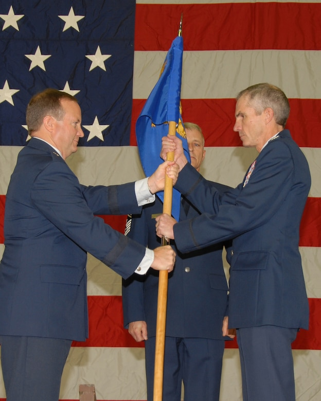BG Don Haught hands the guidon to incoming Wing Commander Col Dennis Grunstad at the change of command ceremony for the 153d Airlift Wing