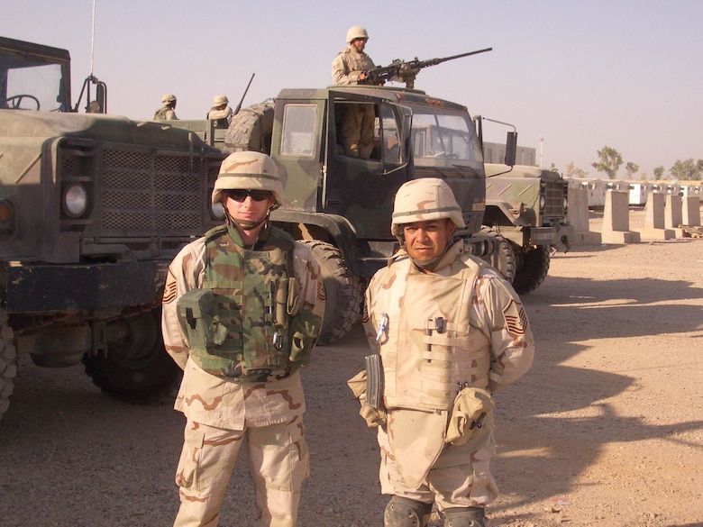 Convoy team members with body armor typically worn on missions.  In the background is one type of gun truck with a .50-cal machine gun position in the cab. (U.S. Air Force photo)
