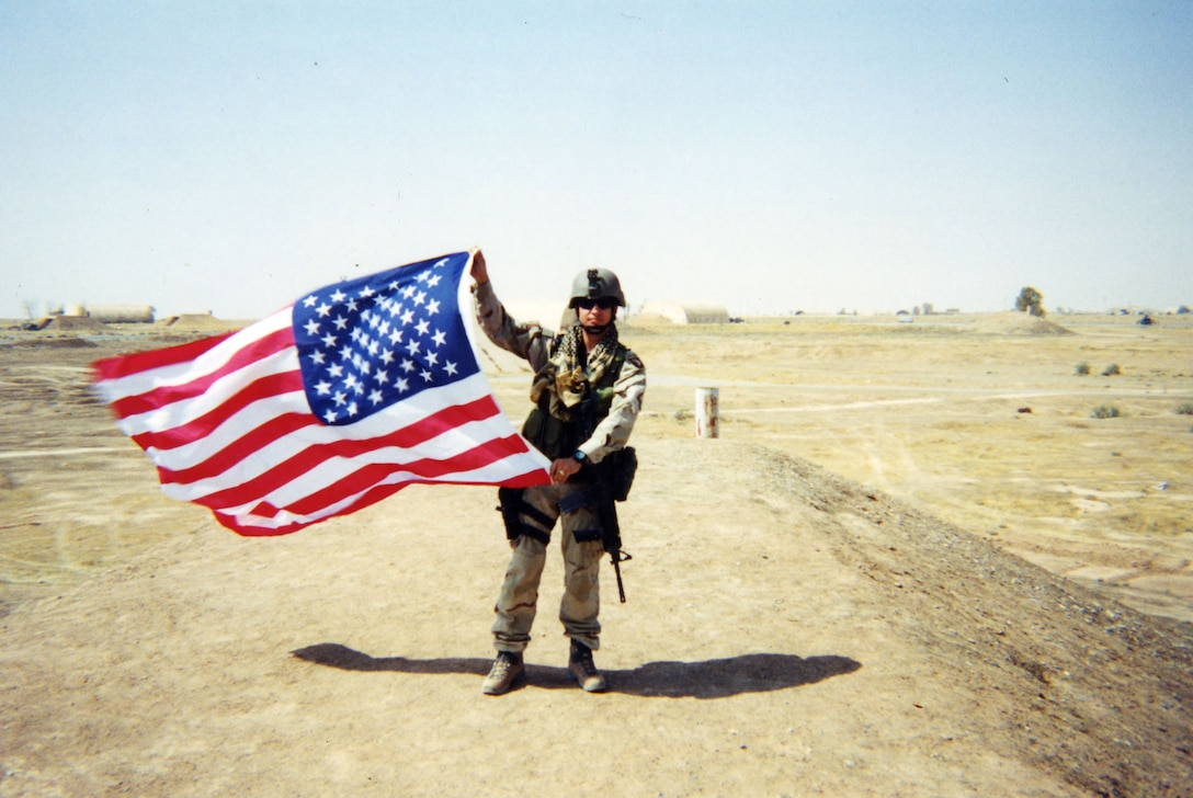 "Staff Sgt. Sean Bailey waving a U.S. flag at ""Q-West"" (Qayyarah Airfield West), about 180 miles north of Baghdad. Bailey served two tours as a JTAC in Iraq. (U.S. Air Force photo)"