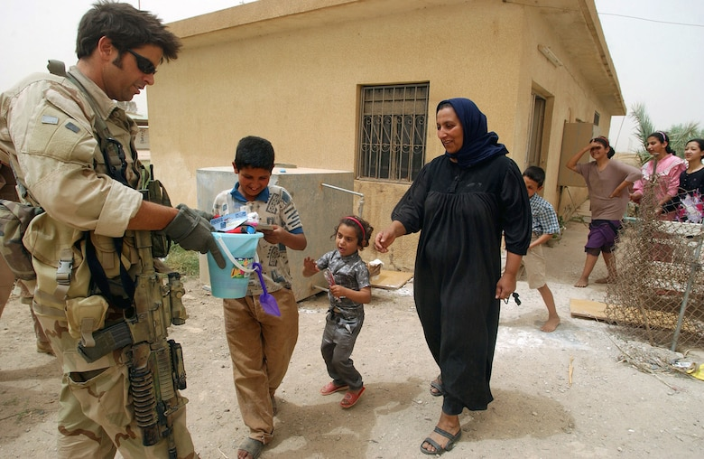 Combat Controller Staff Sgt. David Overton, passing out candy and toys to Iraqi children in Baghdad. (U.S. Air Force photo)