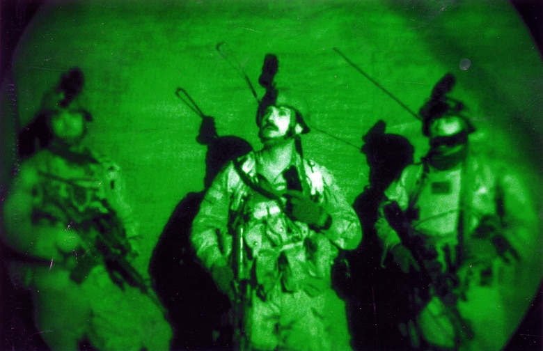 Air Force JTAC scanning the rooftops for snipers during a pre-dawn raid in Fallujah, Iraq, in November 2003. The photo was taken through night vision goggles. (U.S. Air Force photo)
