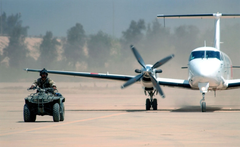 Staff Sgt. Jason Beyer, a Special Operations Weather Team member, escorts the first civilian aircraft to land on the commercial runway at Baghdad International Airport on April 24, 2003. Its cargo was Red Cross personnel and medical supplies. (U.S. Air Force photo)