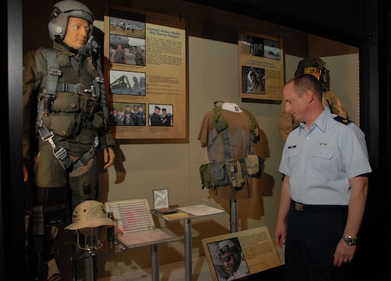 "DAYTON, Ohio -- Maj. Steve Raspet looks at the mannequin that represents him and some of the artifacts he donated as part of the new ""Warrior Airmen"" exhibit at the National Museum of the U.S. Air Force.  Maj. Raspet, a 354th Fighter Squadron A-10 pilot, was the first Airman to have the Combat Action Medal pinned on.  (U.S. Air Force Photo)"