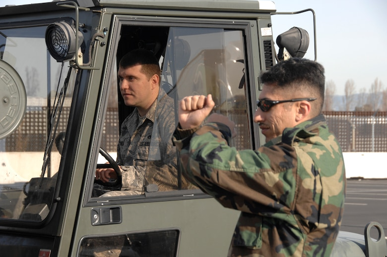"""129th Aerial Port Flight personnel perform safety training at Moffett Federal Airfield, Jan. 4. Senior Airman Razvan Sonea operates a forklift while Staff Sgt. Felipe Mancera demonstrates safety procedures. The 129th Logistics Readiness Squadron's Aerial Port Flight stood up Nov. 1, 2008. 129th Aerial Port personnel, also known as """"Port Dogs,"""" are specialized Airmen trained to manage in-transit passenger and cargo movements for state directed missions and AEF deployments, redeployments, and exercises. (U.S. Air Force photo by Senior Airman Joshua Kauffman)(RELEASED)"""
