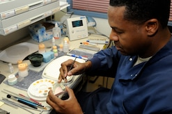 Tech. Sgt. Paul Foreman, 305th Dental Squadron lab technician, hand paints a porcelain partial denture to match Jan 9 at the Dental Clinic. The Dental lab has the latest state-of-the-art equipment; dentures now only take eight hours to make compared to the six weeks they used to take. (U.S. Air Force photo/Wayne Russell)
