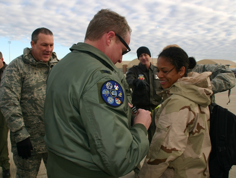 Staff Sergeant Nicole Copeland, 552nd Operations Support Squadron, is awarded her stripe by Col. George Carpenter, commander, 552nd Operations Group, as she disembarked the jet that brought her back from her latest deployment January 14, 2009.