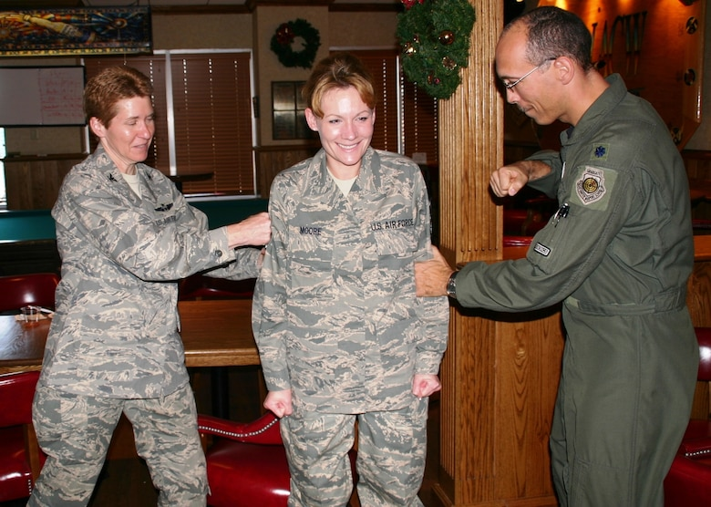Technical Sergeant Rachel Moore, 552nd Air Control Wing, was caught off guard at the Wing Staff Holiday Party with a stripe promoting her to master sergeant for her consistent record of excellence. Col. Pat Hoffman, commander, 552 ACW, and Lieutenant Col. Carson Elmore, director of staff, 552 ACW give her the traditional congratulatory punch.