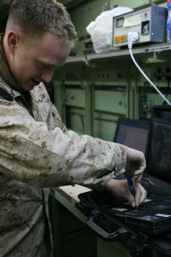 Lance Cpl. Christopher Jourden, a maintenance technician from RCT-8 communications section, removes a hard drive from a broken laptop.  Jourden says as a technician he does a substantial amount of work on computers.  Properly working computers are a key factor in ensuring that Marines are able to transfer and receive information.