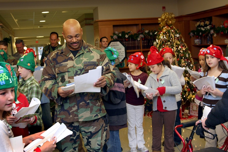 Staff Sgt. Mario Gray carols with the fourth graders from the Seaview School during the New Jersey Air Guard's visit to Vineland Veterans Memorial Home on Dec. 17. Photo by Tech. Sgt. Mark Olsen, 177th FW/PAO.
