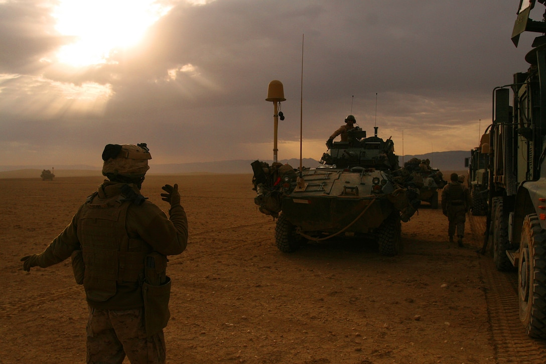 """Cpl. Matthew R. Adams, a logistics vehicle system operator with 1st Light Armored Reconnaissance Battalion guides a light armored vehicle in for for fuel during a resupply mission north of the Sinjar Mountains, Iraq. """"Interdicting smuggling and infiltration of foreign fighters moving into Mosul was a great success,"""" said Lt. Col. Scott D. Leonard, commanding officer for 1st LAR Bn. """"While doing this we were able to get back to our roots as a light armored reconnaissance battalion, by operating independently; in a very austere environment; with a very small support footprint."""""""