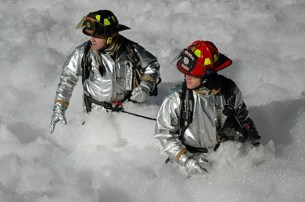 SHAW AIR FORCE BASE, S.C. -- (Lt.) Shayne Carder and Staff Sgt. Bradley McCroskey, 20th Civil Engineer Squadron firefighters, work their way through the foam in Hangar 1200 Jan. 17. the fire surpression system in the Hangar was activated Jan. 17. The quick response from Shaw's Airmen resulted in minimal damage to Air Force assets. (courtesy photo)