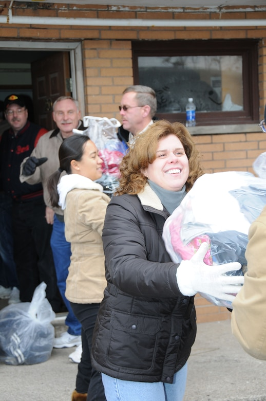 Jeannie Mang helps pass donated clothing down the line during a drop off to the Community Missions in Niagara Falls.