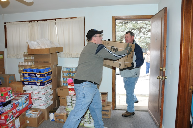 Roger Clark and Dale Selbert bring food donations into the Community Missions on December 16.