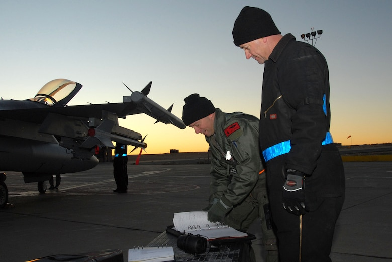 """William E. Orton """"Willy-O"""", a pilot from the 120th Operations Flight, performs pre-flight checks on his F-16 aircraft during an Operational Readiness Inspection, as the Crew Chief looks on."""