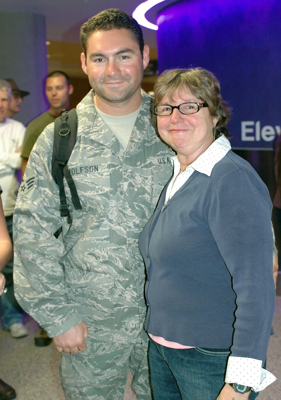 Senior Airman Brent Wolfson reunites with his mother Lynn Harrill who traveled to Tucson from Glendale, Calif., to welcome her son home. Family and friends crowded the baggage claim area at Tucson International Airport to welcome home 28 aircraft maintainers and pilots Jan. 24. The Guardsmen volunteered for tours ranging from 8 months to 30 days in duration. They were given a standing ovation from travelers in the terminal on their way to baggage claim. (Air National Guard photo by Capt. Gabe Johnson)