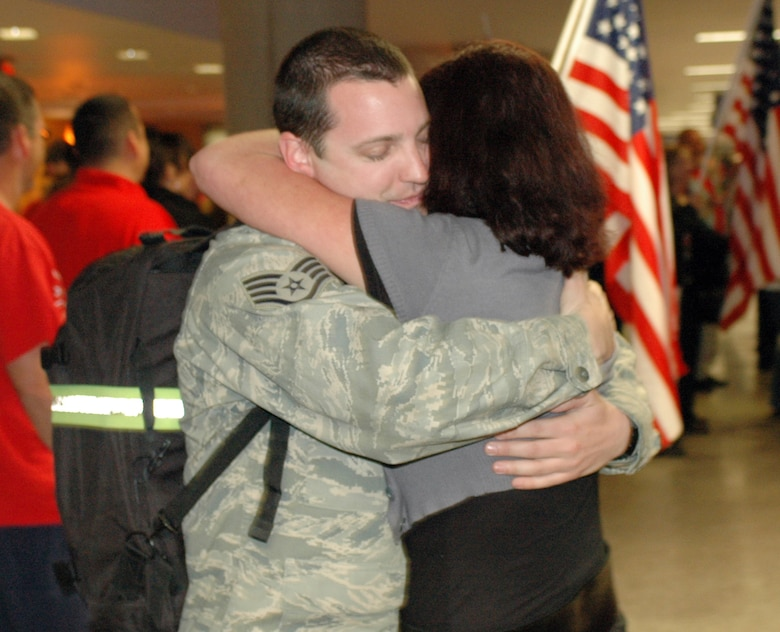 Staff Sgt. TJ Dodson hugs his girlfriend Leta Oranski. Family and friends crowded the baggage claim area at Tucson International Airport to welcome home 28 aircraft maintainers and pilots Jan. 24. The Guardsmen volunteered for tours ranging from 8 months to 30 days in duration. They were given a standing ovation from travelers in the terminal on their way to baggage claim. (Air National Guard photo by Capt. Gabe Johnson)