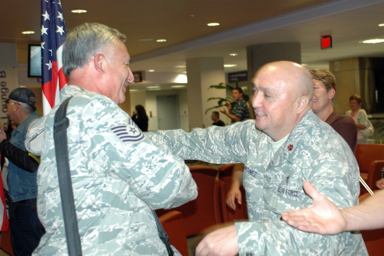 Tech. Sgt. Jaime Aviles is greeted by Chaplain (Maj.) Mike Martinez. Family and friends crowded the baggage claim area at Tucson International Airport to welcome home 28 aircraft maintainers and pilots Jan. 24. The Guardsmen volunteered for tours ranging from 8 months to 30 days in duration. (Air National Guard photo by Capt. Gabe Johnson)