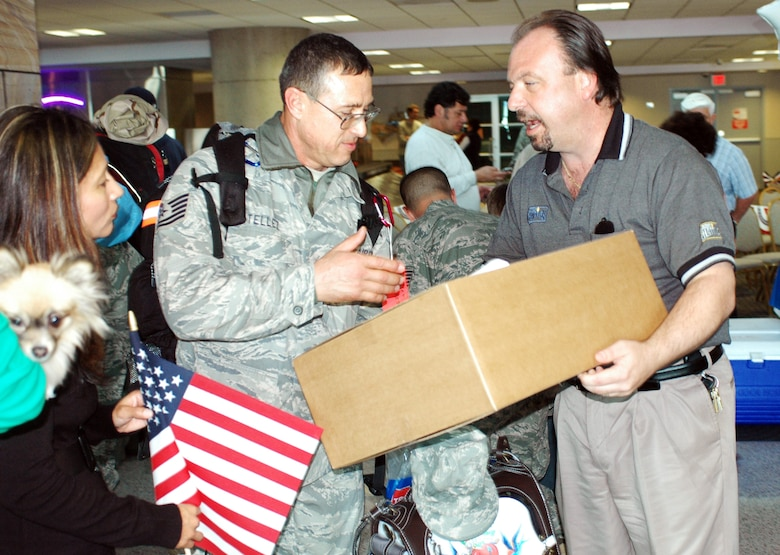 Tech. Sgt. Mike Tellez accepts a box of bread from Rick Cortese of Holsom Bakery Inc. Jan 24 at Tucson International Airport upon his return from Balad Air Base, Iraq. The 162nd Fighter Wing of the Arizona Air National Guard welcomed home Tellez and 27 other aircraft maintainers and pilots after supporting F-16 operations in country. The Arizona baking company gave each returning member a box in appreciation of their service. (Air National Guard photo by Capt. Gabe Johnson)