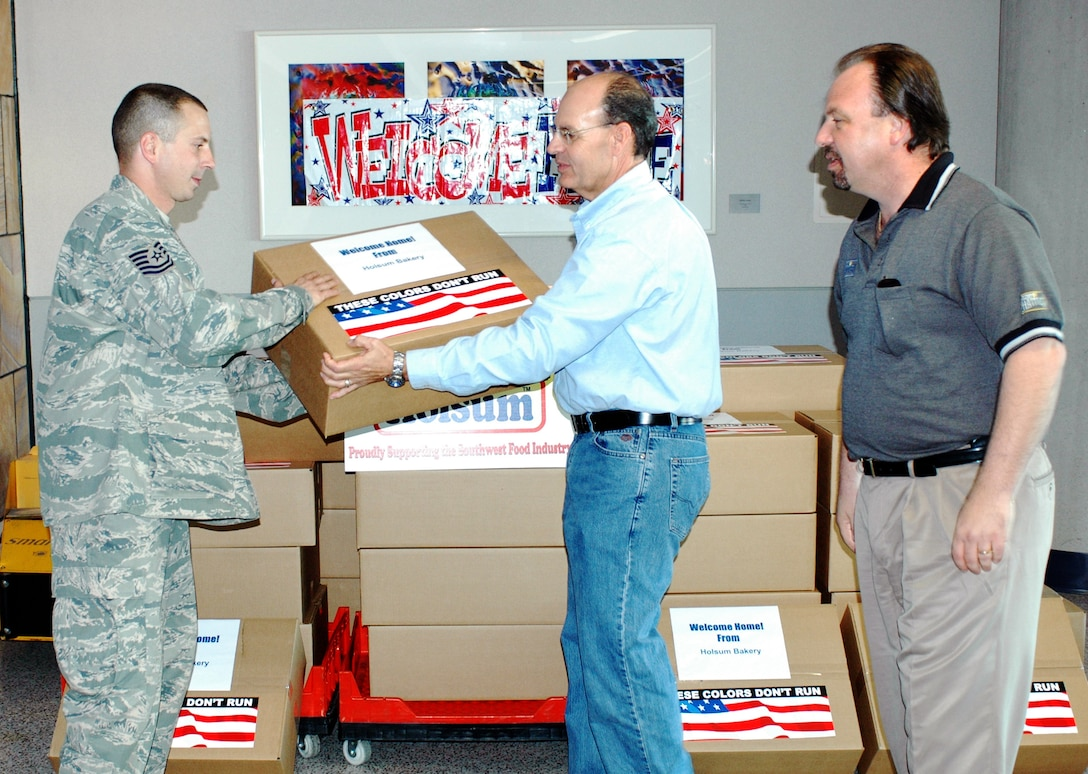 Tech. Sgt. Joe Mazzei accepts a box of bread from Sam Dodson (center) and Rick  Cortese of Holsom Bakery Inc Jan 24 at Tucson International Airport upon his  return from Balad Air Base, Iraq. The 162nd Fighter Wing of the Arizona Air  National Guard welcomed home Mazzei and 27 other aircraft maintainers and  pilots after supporting F-16 operations in country. The Arizona baking company  gave each returning member a box in appreciation of their service. (Air  National Guard photo by Capt. Gabe Johnson)