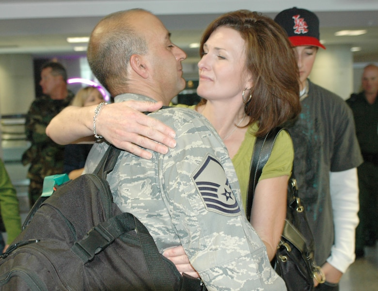 Master Sgt. Ben Ruiz is welcomed home by his wife and son. Family and friends crowded the baggage claim area at Tucson International Airport to welcome home 28 aircraft maintainers and pilots Jan. 24. The Guardsmen volunteered for tours ranging from 8 months to 30 days in duration. (Air National Guard photo by Capt. Gabe Johnson)