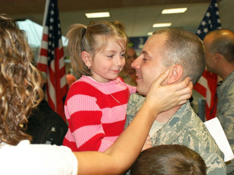 Tech. Sgt. Joe Mazzei hugs his daughter Morgan, 5, upon his return home Jan. 24, after a four-month deployment to Balad Air Base, Iraq. Family and friends crowded the baggage claim area at Tucson International Airport to welcome home 28 aircraft maintainers and pilots. The Guardsmen volunteered for tours ranging from 8 months to 30 days in duration. They were given a standing ovation from travelers in the terminal on their way to baggage claim. (Air National Guard photo by Capt. Gabe Johnson)