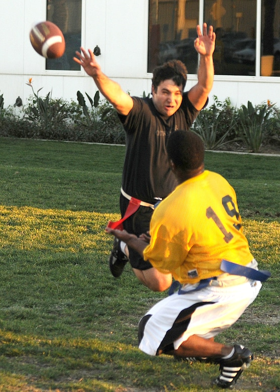 Mike Moore (in black), Team Aerospace, makes a play for the ball in hopes of deflecting a pass thrown to Master Sgt. Shayne Pratt, 61st Medical Group, during their game in the Intramural Flag Football Championship, Jan. 15. The Medical Group won 38-31. (Photo by Stephen Schester)
