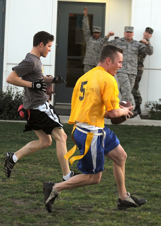 Staff Sgt. Jacob Wilson (in yellow), 61st Medical Group, crosses the goal line to score a touchdown with pursuit from Shaun Brown, Team Aerospace, Jan. 15. Col. Brian Decker (background center), 61st Medical Group commander, and co-workers cheer on during the Medical Groups victory over Aerospace in the Intramural Flag Football Championship game 38-31. (Photo by Stephen Schester)