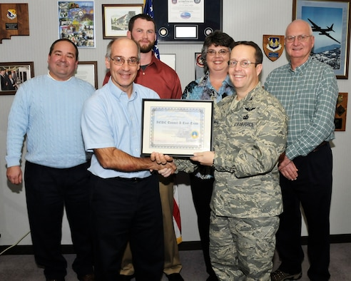Paul Jalbert, Aerospace Testing Alliance (ATA) project manager, and Col. James Jolliffe, 704th Test Group commander, hold a certificate of appreciation that was presented by NASA for the work done on the NASA Ares Stage Separation Test in VKF Tunnel A in July 2008. According to Jalbert, this test was important to NASA because the stability and control data during the booster and upper stage separation will be used to support the Ares I-X flight later this year. Pictured from left to right: Back row, from left, Lyle Sissom, instrumentation engineer, Kevin Boyce, test operations engineer, Janet Feller, programming and data reduction and Win Phipps, AEDC Air Force project manager. ATA is the support contractor for AEDC. (Photo by Rick Goodfriend)