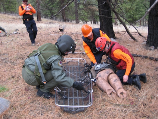 "Capt. Mitchell Parrish, 341st Medical Operations Squadron flight surgeon (left), participates in a search and rescue exercise with the Missoula County Search and Rescue team near Missoula, Mont., November 2008. The crews attempt to safely roll a ""dummy"" victim into a ""stokes litter,"" which is then hoisted in the air to the helicopter hovering above. At Malmstrom, flight surgeons and flight nurses are required to accomplish one day and one night hoist per calendar year for training. (U.S. Air Force photo/Capt. David Oettel)."