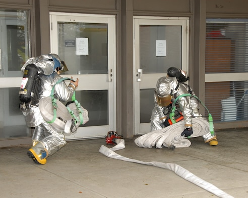 Members of the 143d Airlift Wing Fire Department respond to a call of smoke in the headquarters building during an annual Anti-Terrorism Exercise held at the 143d AW, Quonset Air National Guard Base, North Kingstown, Rhode Island. (USAF photo by MSgt John McDonald) (Released)