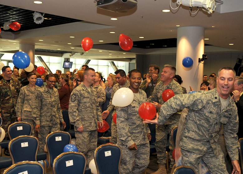 """Los Angeles Air Force Base members, who recently returned from deployment, are welcomed with applause and balloons from the crowd inside Los Angeles AFB Gordon Conference Center at the start of the """"SMC Welcome Home Airmen Celebration"""" ceremony, Jan. 29. (Photo by Stephen Schester)"""