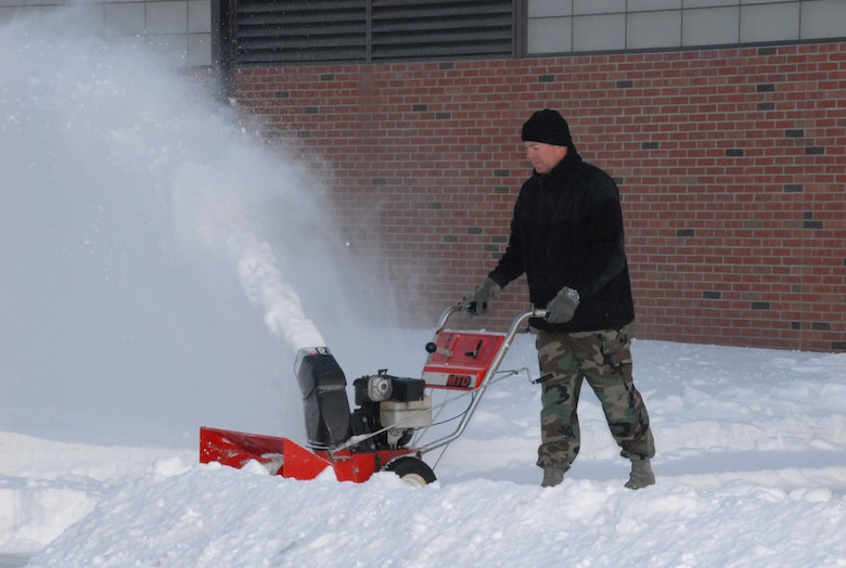 SCOTT AIR FORCE BASE, Ill. - Master Sgt. Terry Szwet, the aircraft structural maintenance shop supervisor with the 126th Maintenance Squadron, works to clear a path through more than five inches of snow that piled up during the two-day winter storm that caused Scott AFB to be minimally manned.  The 126th MXS is assigned to the 126th Air Reufeling Wing, Scott AFB, Ill., and is part of the Illinois Air National Guard. (U.S Air Force photo by Staff. Sgt. Jessica Briney)