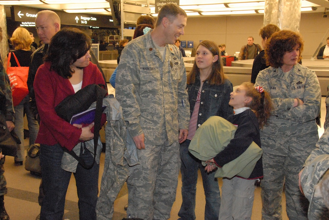 Major Tim Markowitz and his wife, Meridth, talk to their daughters, Olivia and Grace, upon return from a six-month deployment to Afghanistan.  Maj. Markowitz worked on a six-man Facilities Engineer Team at a remote Forward Operating Base with the Army.